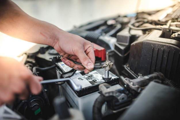 car-mechanic-is-about-remove-battery-replace-new-battery-car-car-repair-shop_140555-26.jpg